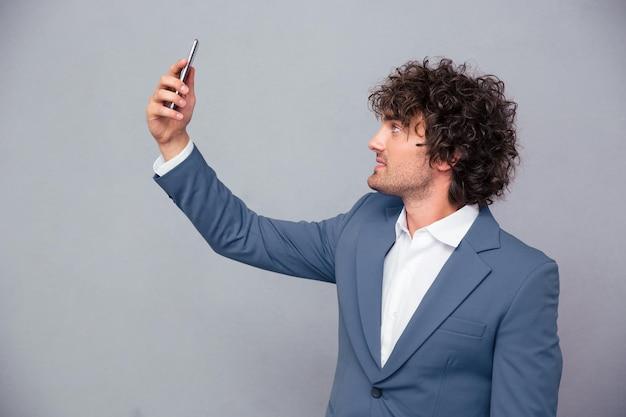Porträt eines schönen geschäftsmannes, der selfie-foto über graue wand macht
