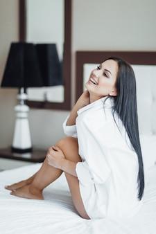 Porträt eines schönen glücklichen brunettemädchens, das im bett sitzt und aufwirft.
