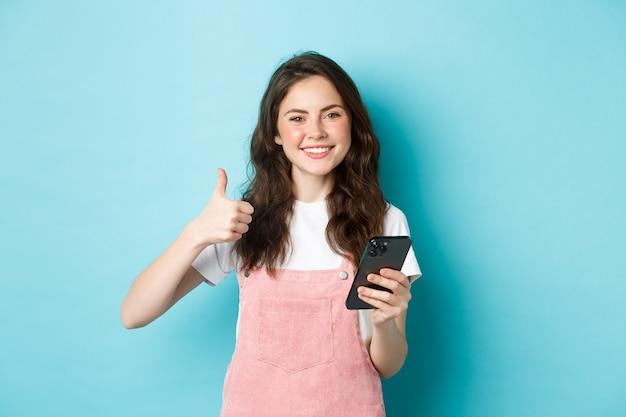 Porträt eines schönen glücklichen mädchens, das daumen nach oben zeigt und smartphone hält, online-shopping, bestellung im internet, zufrieden aussehend, gute app lobend, blauer hintergrund.