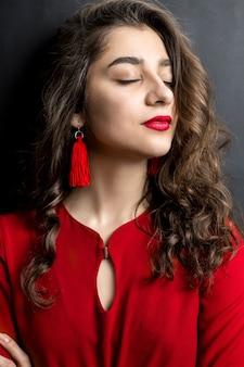 Porträt eines schönen indischen mädchens mit rotem lippenstift und kleid auf einem schwarzen hintergrund