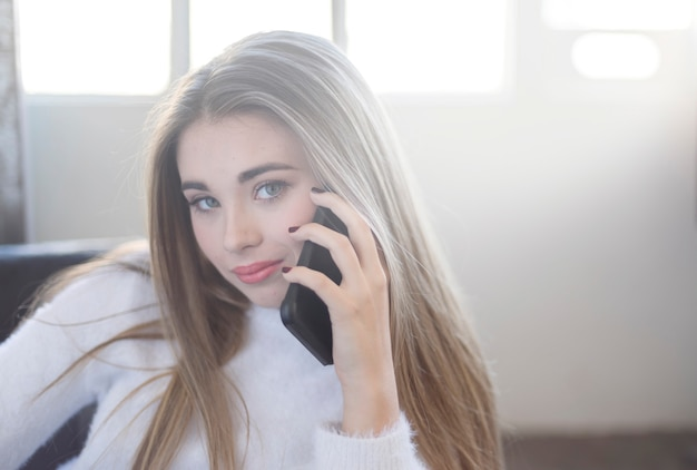 Porträt eines schönen jugendlichen, der an ihrem telefon spricht