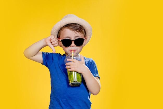 Porträt eines schönen jungen glücklicher europäischer junge in einem hutsommert-shirt mit limonade