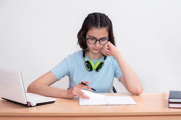 Porträt eines schönen jungen mädchens, das an einem tisch sitzt, hausaufgaben macht oder sich auf eine prüfung auf weißem hintergrund vorbereitet. online-lernkonzept