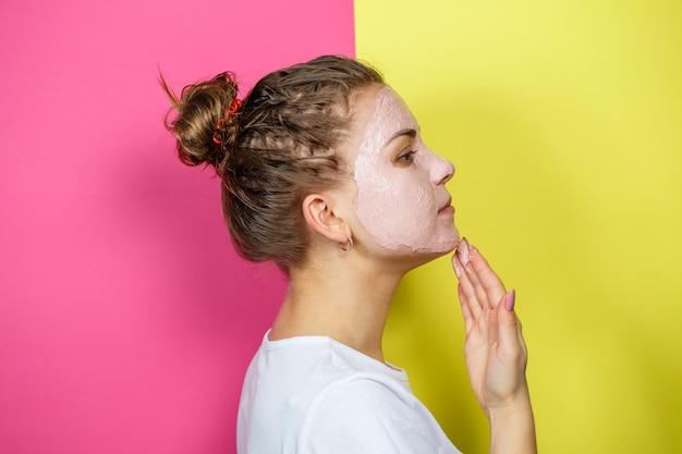 Porträt eines schönen jungen mädchens, das eine erfrischende maske auf ihr gesicht legt, um die haut zu verjüngen und zu straffen. schönheitsbehandlungen