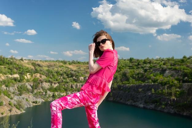 Porträt eines schönen jungen mädchens, das mit rosafarbenem outfit in einem see posiert