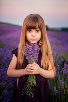 Porträt eines schönen jungen mädchens in einem violetten kleid mit einem blumenstrauß des lavendels in den strahlen der untergehenden sonne