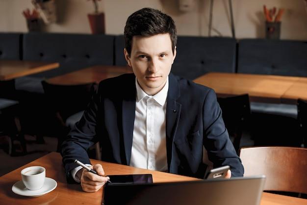 Porträt eines schönen jungen managers, der auf einem schreibtisch sitzt, der arbeitet, während in einem café ist, das die kamera selbstbewusst betrachtet.