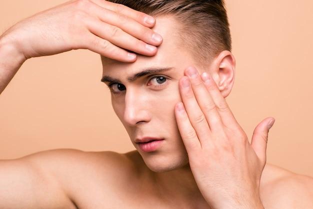 Porträt eines schönen jungen mannes lokalisiert auf pastellbeige