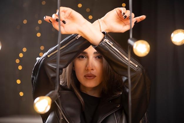 Porträt eines schönen jungen modells in der schwarzen lederjacke, die nahe lampen aufwirft.