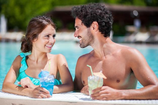 Porträt eines schönen jungen paares, das ein cocktail auf dem poolside genießt