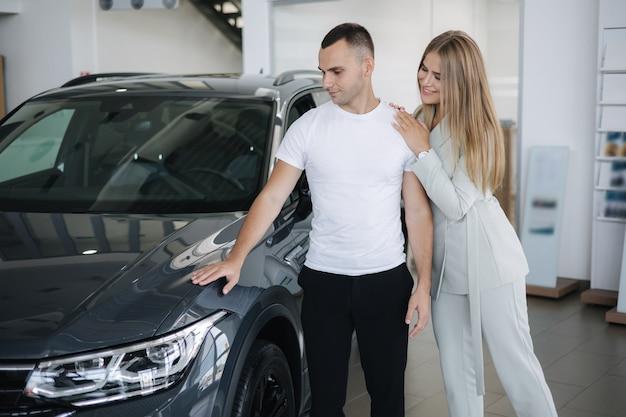 Porträt eines schönen jungen paares glücklich nach dem kauf eines neuen autos von der autohausfrau hus ihr mann