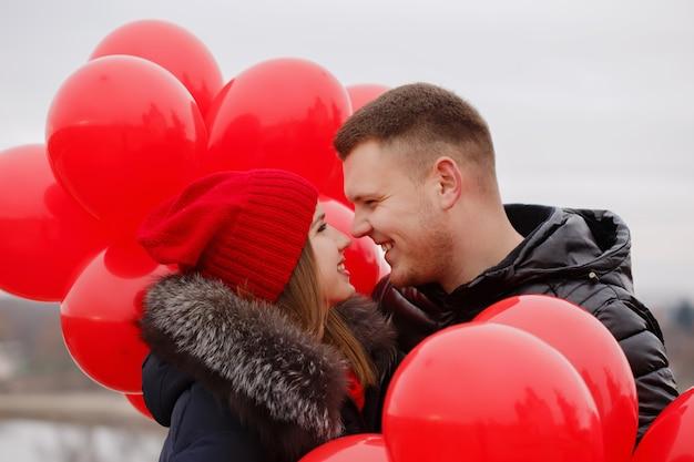 Porträt eines schönen jungen paares mit roten luftballons