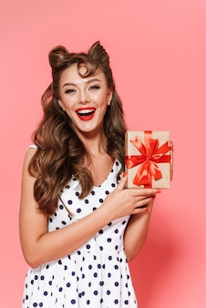 Porträt eines schönen jungen pin-up-mädchens im kleid, das isoliert steht und geschenkbox zeigt