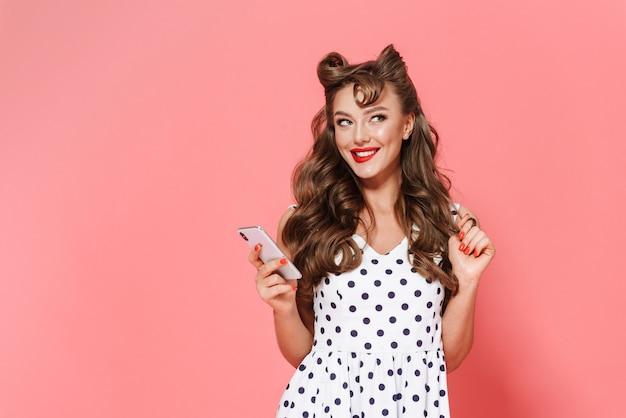 Porträt eines schönen jungen pin-up-mädchens im kleid, das isoliert steht, unter verwendung des mobiltelefons