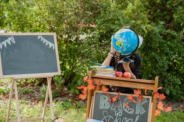 Porträt eines schönen jungen schulmädchens, das an einem schreibtisch sitzt