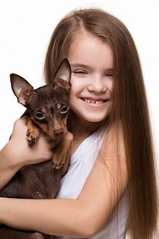 Porträt eines schönen kaukasiers des jungen mädchens, das mit einem netten terrierhündchen kuschelt