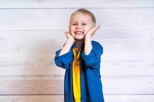 Porträt eines schönen kinderjungen in der gelben t-shirt und in der denimjacke, hemd. junge, der auf einem weißen hölzernen hintergrund steht. 5 jahre alter junge. hände in der nähe von gesicht.