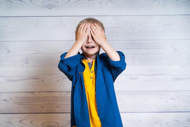 Porträt eines schönen kinderjungen in der gelben t-shirt und in der denimjacke, hemd. junge, der auf einem weißen hölzernen hintergrund steht. 5 jahre alter junge. schließt die augen mit den händen.