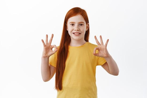 Porträt eines schönen kindes, mädchen mit rotem kopf und sommersprossen zeigt okayzeichen und lächelt glücklich