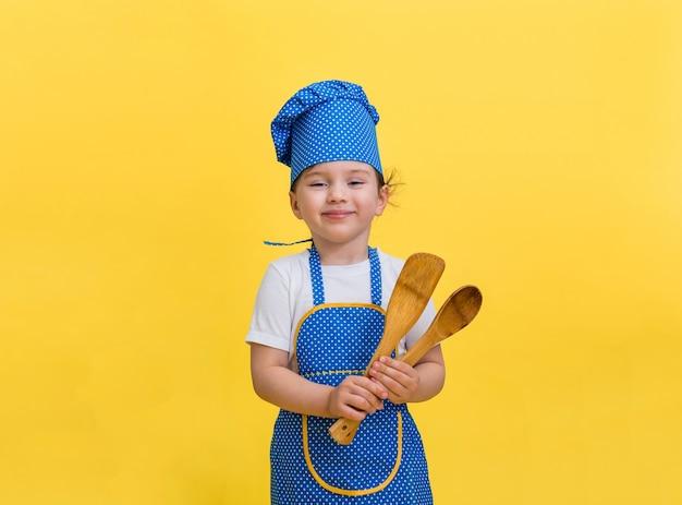 Porträt eines schönen kleinen mädchens, das als koch verkleidet ist und einen hölzernen spatel und einen löffel hält. nettes mädchen in einer blauen und gelben kochschürze und kappe auf einem gelben raum mit einem kopienraum.