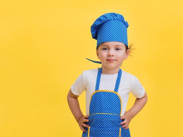 Porträt eines schönen kleinen mädchens, das als lächelnder koch gekleidet ist. nettes mädchen in einer blauen und gelben kochschürze und kappe auf einem gelben raum mit einem kopienraum.