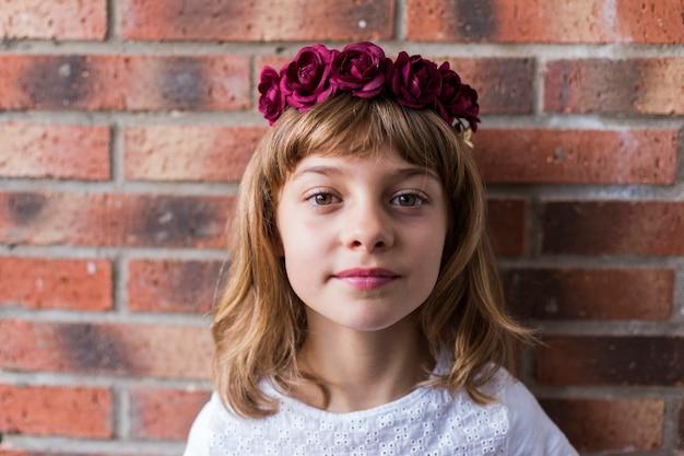 Porträt eines schönen kleinen mädchens, das eine rote kronenrosen auf ihrem kopf trägt. lebensstil