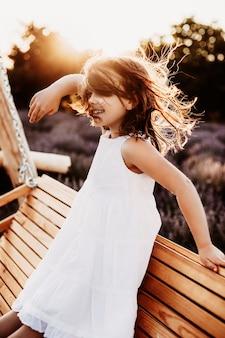 Porträt eines schönen kleinen mädchens, das im wind gegen sonnenuntergang lächelt, gekleidet im weißen kleid, das auf einer hölzernen schaukel in einem lavendelfeld sitzt.