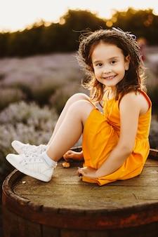 Porträt eines schönen kleinen mädchens gekleidet im gelben kleid, das auf einem hölzernen fass sitzt, das kamera betrachtet, die einen kranz des lavendels gegen sonnenuntergang lächeln sieht.