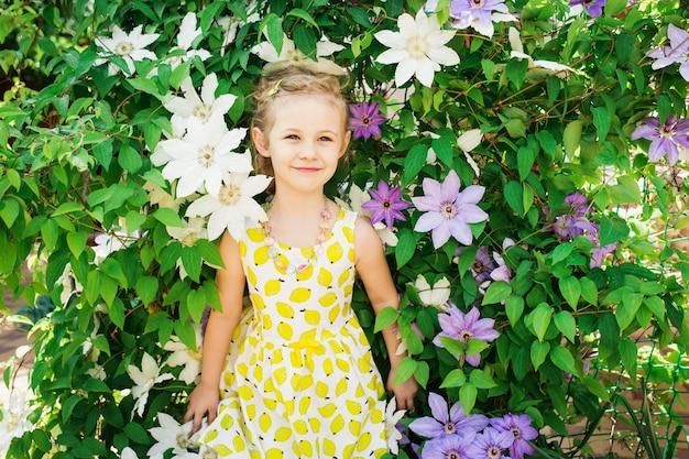 Porträt eines schönen kleinen mädchens im sommerkleid, clematisblumen