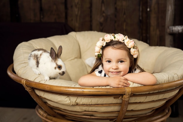 Porträt eines schönen kleinen mädchens in einem blumenkranz. ein mädchen mit einem niedlichen flauschigen weißen osterhasen.