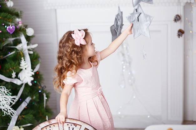 Porträt eines schönen kleinen mädchens in einem rosa kleid mit weihnachtsschmuck