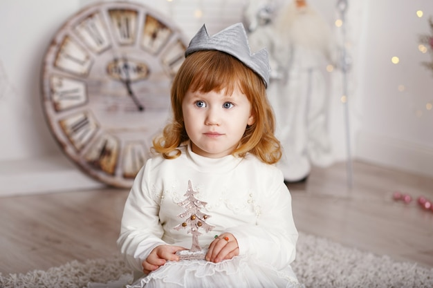 Porträt eines schönen kleinen mädchens in einem weißen kleid und einer krone im innenraum mit weihnachtsschmuck. kleine prinzessin