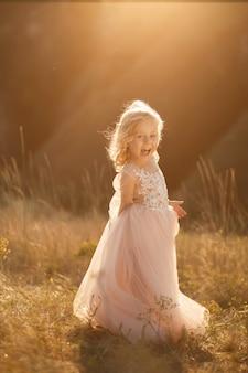Porträt eines schönen kleinen prinzessinmädchens in einem rosa kleid bei sonnenuntergang