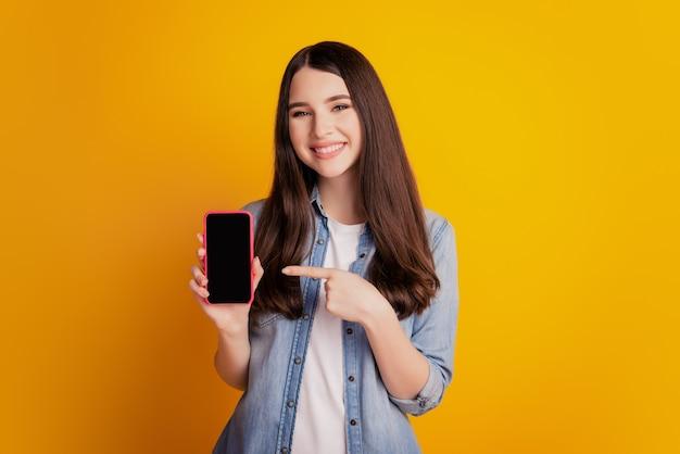 Porträt eines schönen lächelnden glücklichen mädchens halten telefon direkter finger-touchscreen-leerraum auf gelbem hintergrund