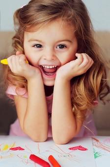 Porträt eines schönen lächelnden kindes des europäischen auftrittes mit dem gelockten haar auf dem hintergrund der zeichnungen der kinder.