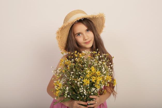Porträt eines schönen langhaarigen mädchens in einem strohhut mit wilden herbstblumen in den händen