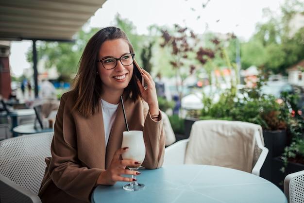 Porträt eines schönen mädchens am café, sprechend auf smarthphone, draußen.