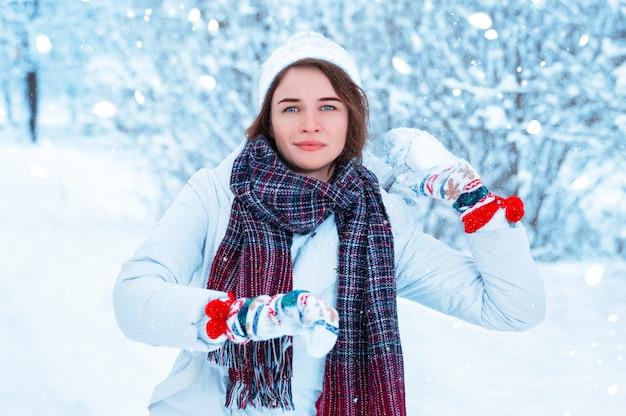 Porträt eines schönen mädchens, das einen schneeball wirft