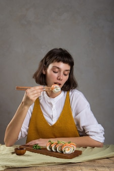 Porträt eines schönen mädchens, das sushi-rolle mit lachs mit stäbchen isst