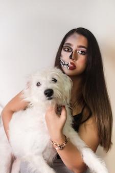 Porträt eines schönen mädchens im halloween-make-up mit ihrem hund auf weißem hintergrund.