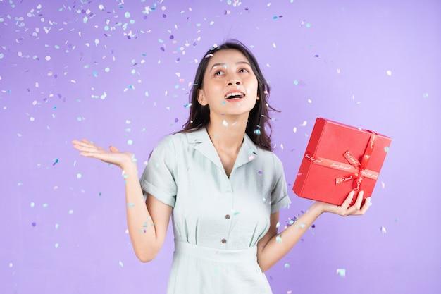 Porträt eines schönen mädchens in der hand mit roter geschenkbox und feiern unter konfettiregen, isoliert auf violettem hintergrund