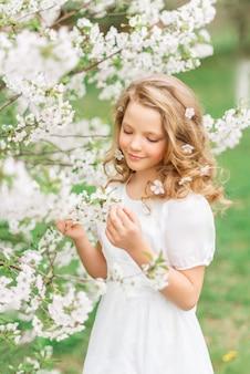 Porträt eines schönen mädchens in einem blühenden garten im frühjahr. nettes baby mit weißen blumen im haar.
