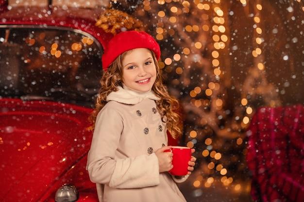 Porträt eines schönen mädchens in einer roten baskenmütze mit einem becher in ihren händen vor dem hintergrund eines roten neujahrsautos
