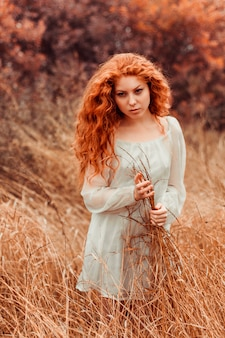 Porträt eines schönen mädchens mit dem roten haar auf dem gebiet