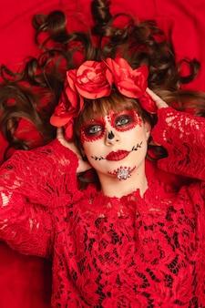 Porträt eines schönen mädchens mit dia de los muertos make-up und kleidung, die auf einem roten hintergrund liegen.
