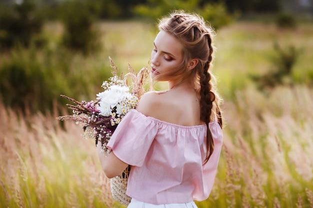 Porträt eines schönen mädchens mit einem blumenstrauß. sommer fotoshooting