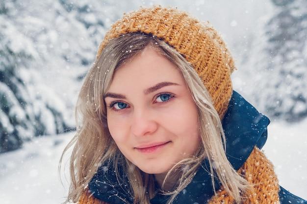 Porträt eines schönen mädchens mit hut auf dem hintergrund der winterlandschaft