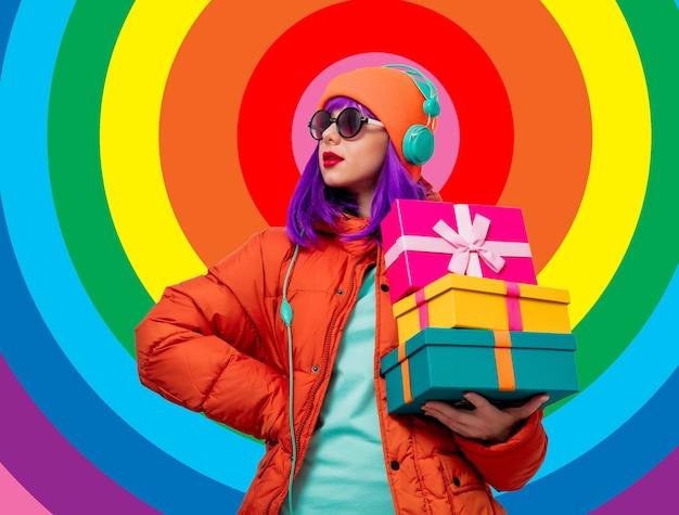 Porträt eines schönen mädchens mit lila haaren in orange hut und jacke und mit kopfhörern und geschenkboxen auf regenbogenhintergrund. trendiger stil