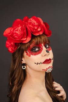 Porträt eines schönen mädchens mit make-up dia de los muertos mit grauem hintergrund.