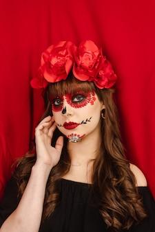 Porträt eines schönen mädchens mit make-up dia de los muertos mit rotem hintergrund.